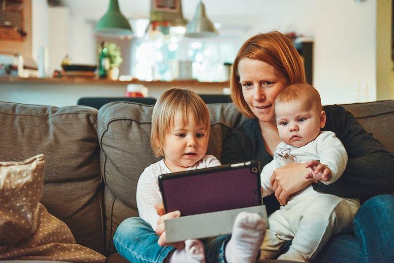 Mama z dwójką dzieci oglądają coś na tablecie